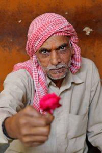 A flower vendor in Old Delhi's flower market offering a rose
