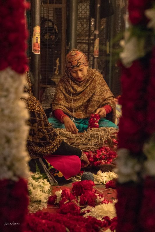 A woman in the flower market making garlands